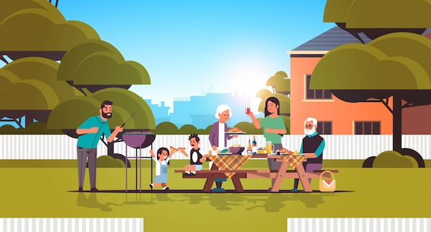 Multi generation family preparing hot dogs on grill happy grandparents parents and children having fun backyard picnic barbecue party concept flat full length horizontal