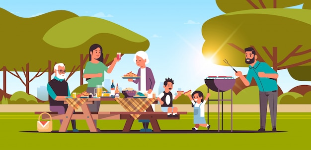 Multi generation family preparing hot dogs on grill happy grandparents parents and children having fun picnic barbecue party concept summer park landscape background flat full length horizontal