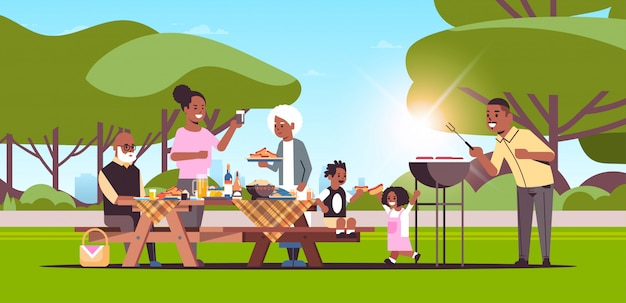 Multi generation family preparing hot dogs on grill picnic barbecue party concept summer park landscape background flat full length horizontal