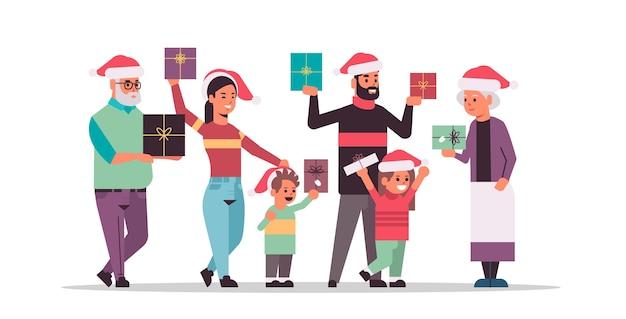 一緒に立っているギフトプレゼントボックスを持つ多世代家族メリークリスマス新年あけましておめでとうございます休日のお祝いのコンセプト祖父母とサンタの帽子をかぶっている子供たちの全長水平ベクトル