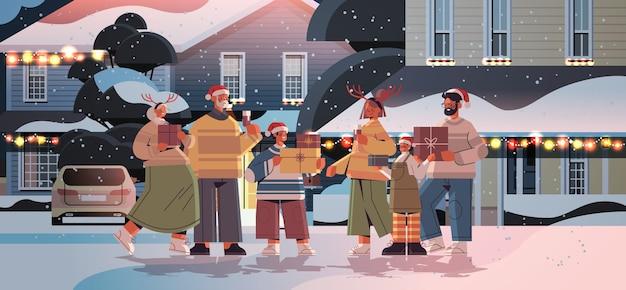 장식 된 집 선물 상자 새 해 복 많이 받으세요 그리고 메리 크리스마스 휴일 축 하 개념 가로 전체 길이 벡터 일러스트 레이 션 근처에 서 선물을 가진 다 세대 가족