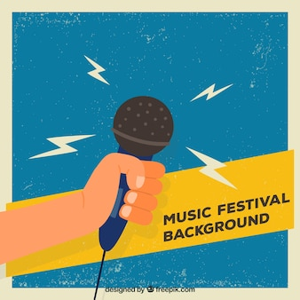 Music festival background with hand holding a microphone
