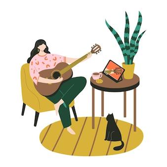 음악 온라인 학습, 교육. 기타 레슨. 젊은 여성이 집에 앉아 태블릿으로 비디오 수업을 보고 기타를 연주하는 훈련을 합니다.