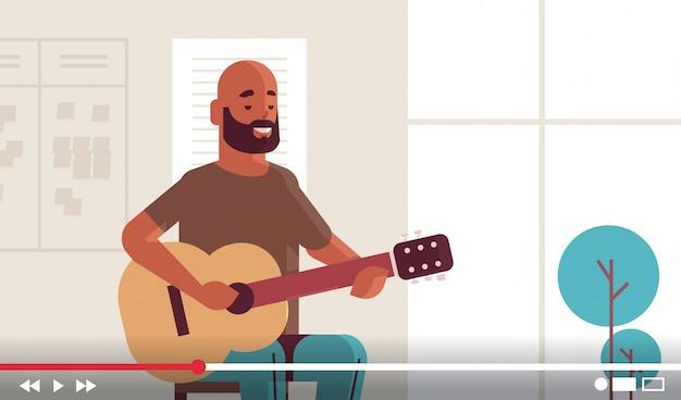 Музыкальный блоггер запись онлайн видео поток для vlog мужской афроамериканец vlogger играть на гитаре блоггинг концепция портрет горизонтальный