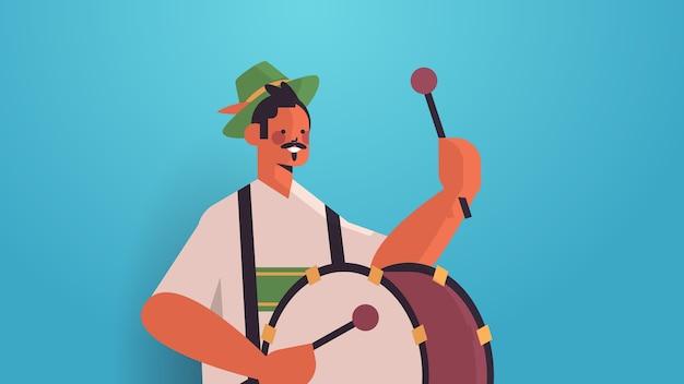 Музыкант играет на барабане на крупнейшем народном фестивале октоберфест концепция празднования вечеринки мужчина в традиционной немецкой одежде веселится