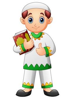 Quranを保持し、親指をあげているムスリムの少年漫画