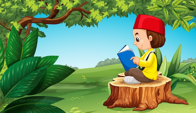 Muslim boy reading book in park