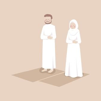 イスラム教徒のカップルが祈りのマットで一緒に祈る練習