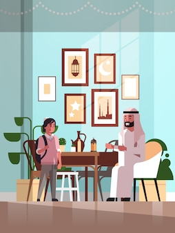 Muslim family celebrating ramadan kareem holy month living room interior arabic father and son in traditional clothes spending time together flat vertical full length