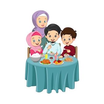一緒においしいイフタール料理を食べているイスラム教徒の家族