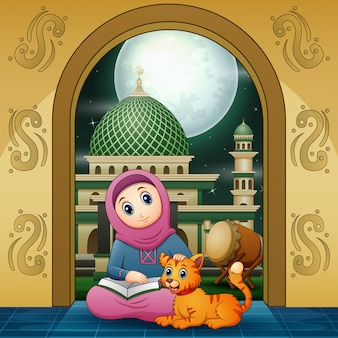 A muslim girl reading a book at the mosque with a cat
