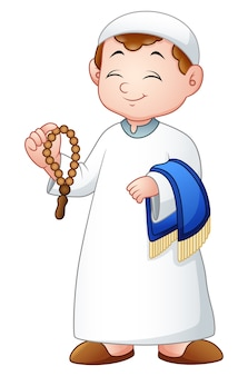 Muslim kid holding praye beads and prayer rug