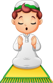 Muslim kid sitting on the prayer rug while praying