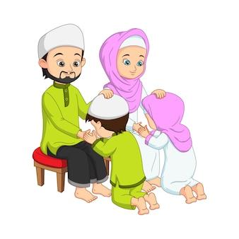 イスラム教徒の子供たちが両親の手にひれ伏してキスをする