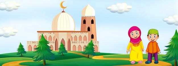 モスクの背景を持つイスラム教徒の子供たち