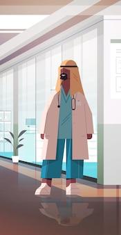 Muslim man doctor in uniform arabic male medical professional standing in hospital corridor medicine healthcare concept full length vertical vector illustration
