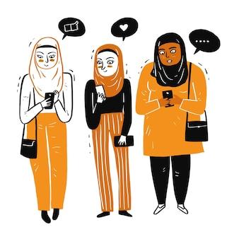 集まったイスラム教徒の女性明るい日にスマホを楽しく使う