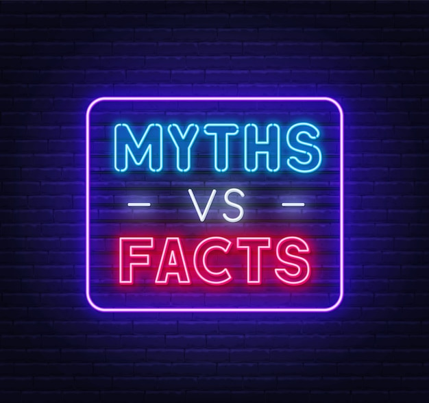 Myths vs facts neon sign on brick wall background.