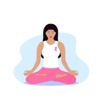 Национальный месяц осведомленности о раке груди. молодая женщина с розовой лентой на груди медитирует.
