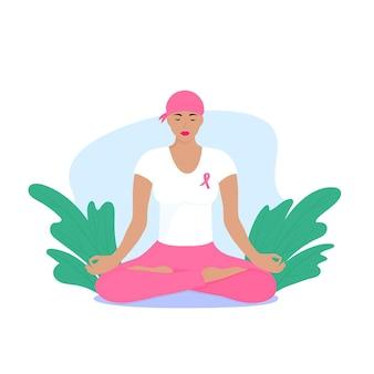 Национальный месяц осведомленности о раке груди. молодая женщина с шарфом на голове и розовой лентой на груди медитирует.