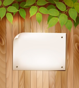Natural wooden background with leaves and a blank piece of paper.