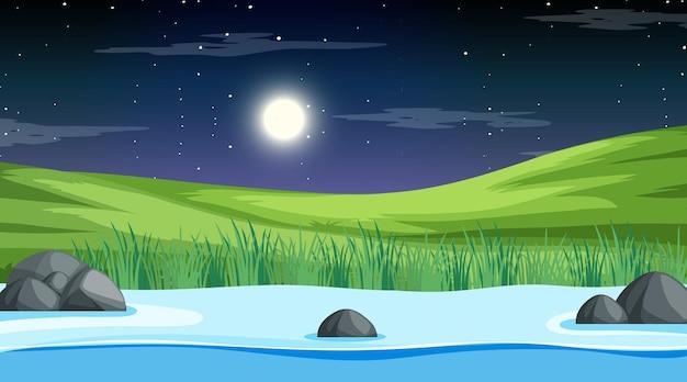 牧草地を流れる長い川と夜景の自然林の風景