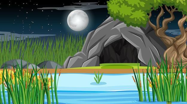 Paesaggio della foresta naturale di notte con grotta in pietra