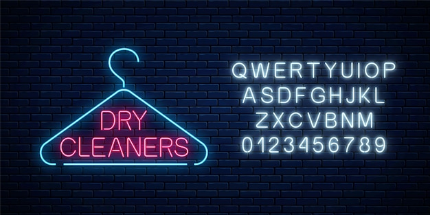 Neon dry cleaners glowing sign with hanger on a dark brick wall