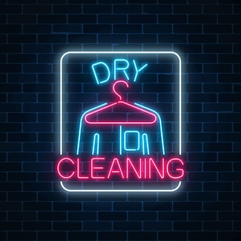 Neon dry cleaners glowing sign with hanger and shirt on a dark brick wall