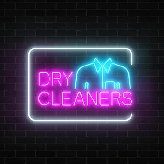 어두운 벽돌 벽 바탕에 사각형 프레임에 셔츠와 함께 서명 네온 드라이 클리너 빛나는.