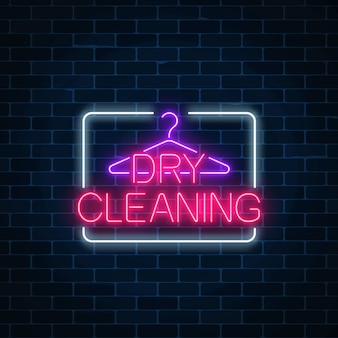 Neon dry cleaning glowing sign with hanger on a dark brick wall