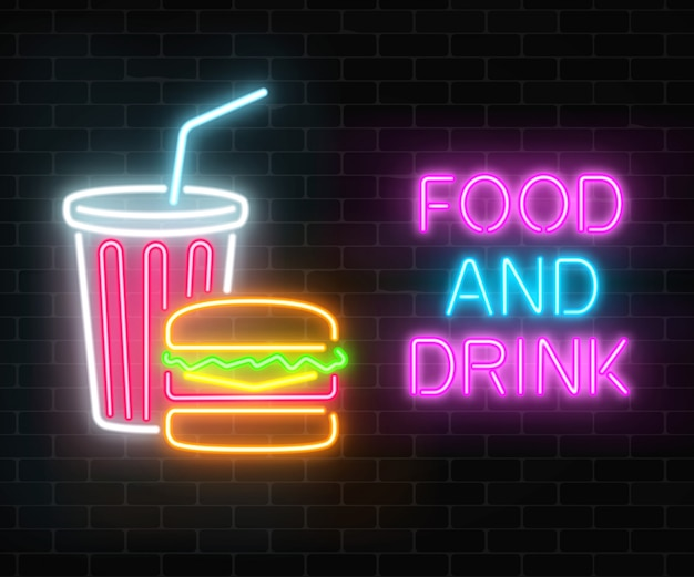 Neon food and drink glowing signboard on a dark brick wall . burger and plastic cup of beverage signs.
