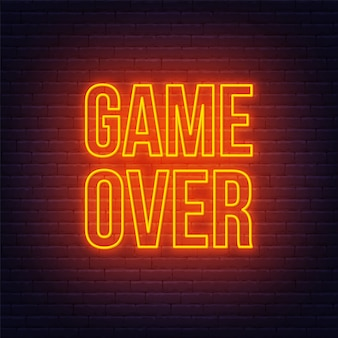 Neon game over sign on brick wall background.