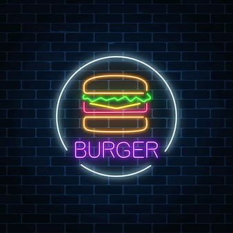 Neon glowing sign of burger in circle frame on a dark brick wall