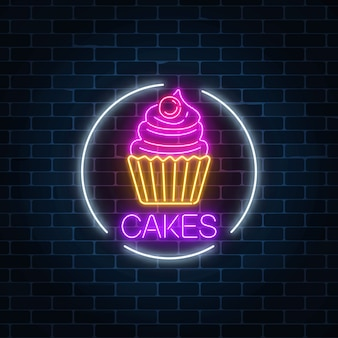 Neon glowing sign of cake with cream and cherry in circle frame on a dark brick wall