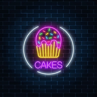 Neon glowing sign of cake with glaze in circle frame on a dark brick wall