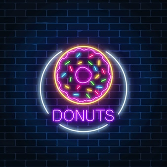 Neon glowing sign of donuts in circle frame on a dark brick wall