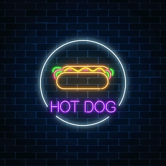Neon glowing sign of hot dog in circle frame on a dark brick wall