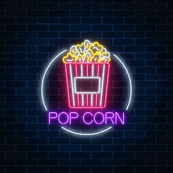 Neon glowing sign of pop corn in circle frame on a dark brick wall