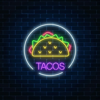 Neon glowing sign of tacos in circle frame on a dark brick wall