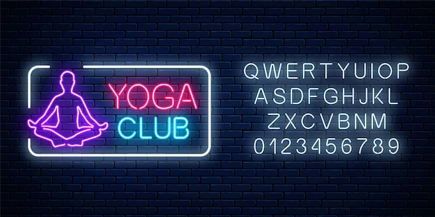 Neon glowing sign of yoga exercices club in rectangle frame with alphabet on dark brick wall