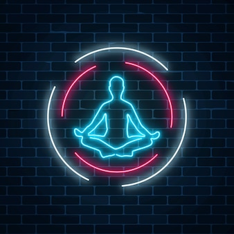 Neon glowing sign of yoga exercices club with lotus pose in circle frames on dark brick wall background.