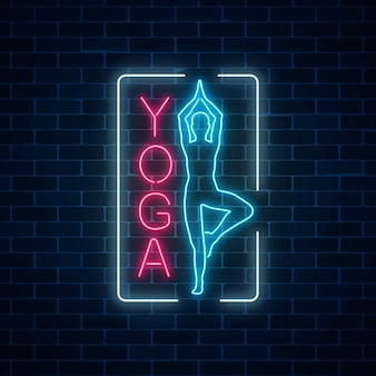 Neon glowing sign of yoga exercices in rectangle frame on dark brick wall background.