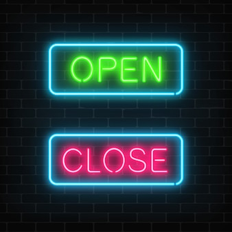 Neon green open and red close glowing signs in geometric shape on a brick wall .
