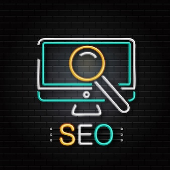 Neon sign of computer and magnifier glass for decoration on the wall background. realistic neon logo for seo. concept of search engine optimization.