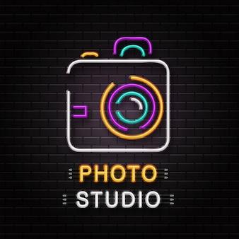 壁の背景に装飾用カメラのネオンサイン。写真スタジオの現実的なネオンのロゴ。写真家の職業と創造的なプロセスの概念。