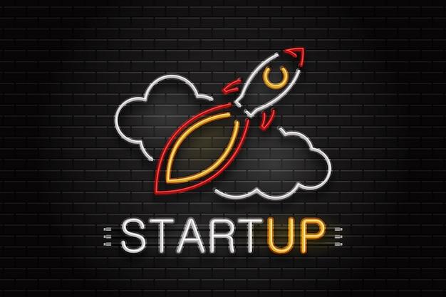 ロケットと壁の背景に装飾用の雲のネオンサイン。スタートアップのための現実的なネオンのロゴ。ビジネスと成功のコンセプト。