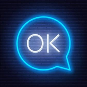 Neon sign ok in speech bubble frame on dark background.