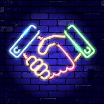 Рукопожатие неоновой вывески. командная работа, сотрудничество или дружба. яркая ночная вывеска на знаке кирпичной стены. иллюстрация реалистичный неоновый значок