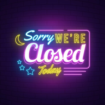 Neon 'sorry we are closed' sign on brick wall